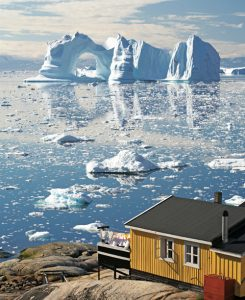 Greenland, Disko Bay, Ilulissat, wooden house with large iceberg in background